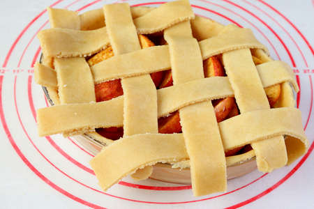 Woven dough on the pie plate for lattice top crust of a homemade apple pie Imagens