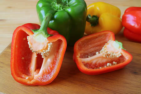 Closeup Cut Red Bell Pepper on Wooden Cutting Board with Green and Yellow Peppers in Background 免版税图像