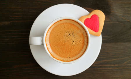 Top View of a Cup of Hot Coffee with Heart Shaped Cookie on Dark Brown Wooden Table for the Concept of LOVE 스톡 콘텐츠