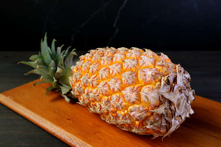 Fresh Ripe Pineapple on a Wooden Cutting Board Isolated on Black Background