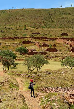 Female Traveler Taking Photos of Piquillacta, Ruins of the Ancient Settlement of Wari Culture in Valle Sur, Cusco Region, Peru