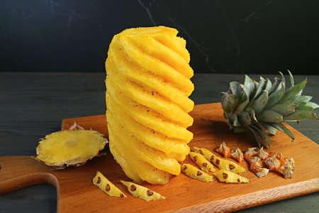 Beautifully peeled and cut fresh ripe pineapple on a wooden cutting board Zdjęcie Seryjne