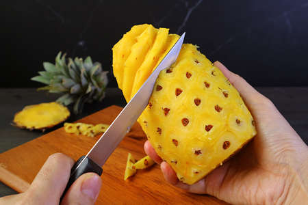 Hand holding knife for peeling and removing the hard and prickly eyes of a fresh ripe pineapple Zdjęcie Seryjne