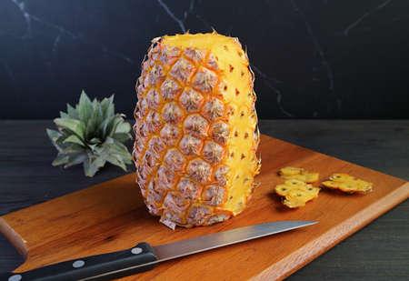 Fresh ripe pineapple being peeled on a wooden cutting board Zdjęcie Seryjne