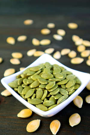 Vertical image of roasted pumpkin seeds with raw seeds scattered around on wooden table