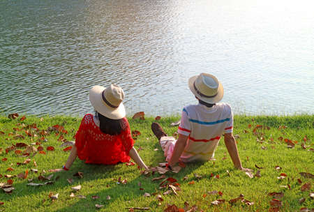 Couple in straw hat relaxing together on the lakeside