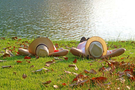 Couple in wide brim hat lying side by side on the sunny waterfront