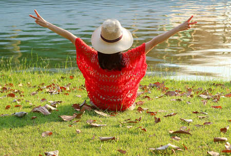 Happy Woman in Straw Hat Raising Arm with V Sign Sitting on the Lakeside