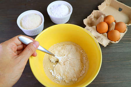 Man's Hand Mixing Ingredients in a Bowl for Baking Whole Wheat Muffins 免版税图像