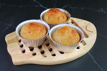 Fresh Baked Homemade Banana Muffins in Molds on a Wooden Breadboard
