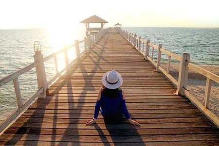 Young Woman in White Hat Sitting on the Wooden Pier