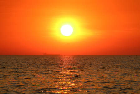 Bright sun on the orange sky setting over the sea