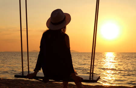 Silhouette of a woman in hat relaxing on the swing at sunset