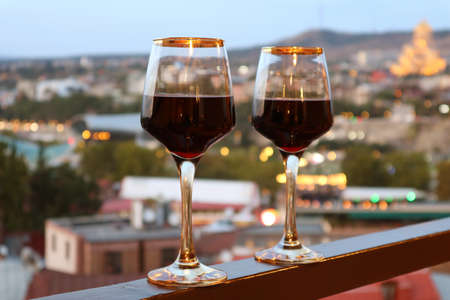 Two Wine Glasses on the Balcony with Blurry Evening City View in Background