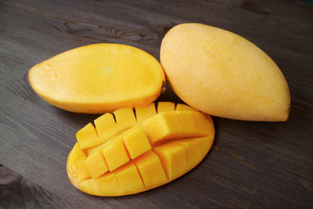 Fresh ripe mango cut in half and crosswise cut with a whole fruit on black