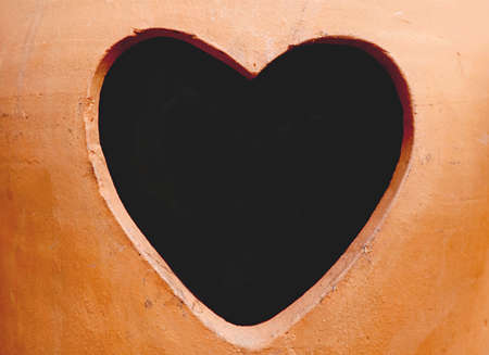 Heart Shape Hole on a Terracotta Vase with Copy Space 免版税图像