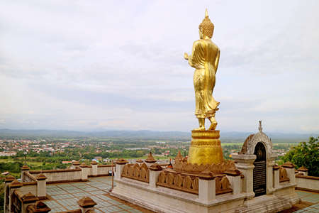 Incredible golden Buddha image in walking posture overlooks the town of Nan, Wat Phra That Khao Noi temple in northern Thailand