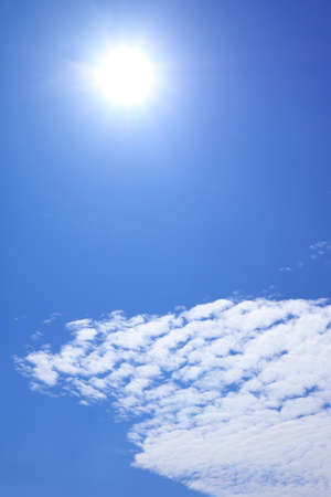 Vertical Image of the Bright Sun Shining above Altocumulus Clouds on Vibrant Blue Sky 免版税图像
