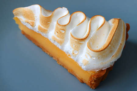 Closeup a Slice of Tasty Lemon Meringue Tart on Blue Plate 免版税图像
