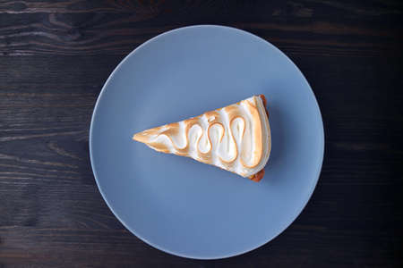 Plate of a Slice of Delicious Lemon Meringue Tart on Black Wooden Background