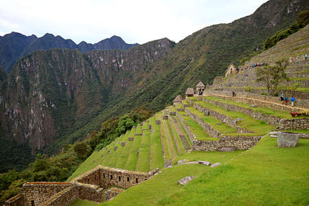 Groups of visitors exploring the archaeological site of Machu Picchu Inca Citadel in Cusco region, Peru, South America