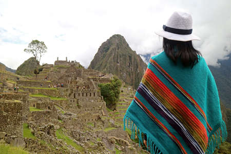 Female Traveler Looking at the Ancient Citadel of Machu Picchu,   in Cusco Region of Peru 免版税图像