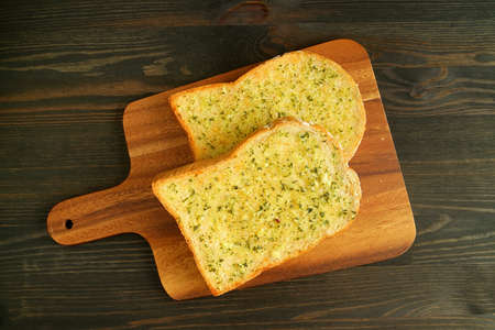 Pair of Delectable Homemade Garlic Butter Whole Wheat Toasts on Wooden Breadboard