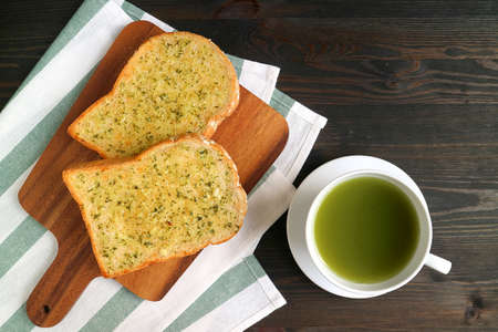 Pair of Garlic Butter Toasts on Breadboard with a Cup of Hot Green Tea on Wooden Table
