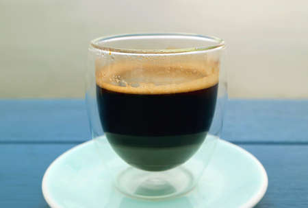 Glass of hot black coffee isolated on blue wooden table