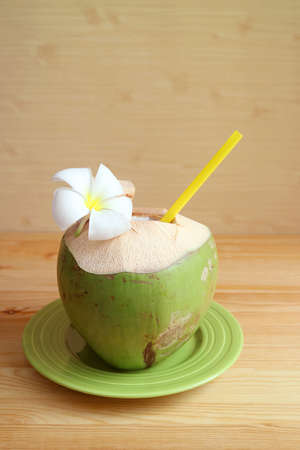 Vertical image of fresh young coconut juice with a blooming Frangipani flower on wooden background