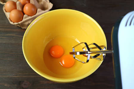 Closeup of Electric Egg Beater Going to Beat aPair of Raw Eggs in Mixing Bowl