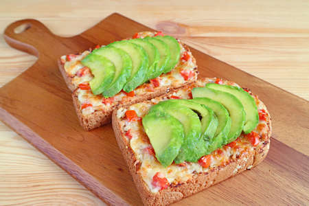 Closeup a pair of homemade grilled cheese toast topped with tomato and avocado on a breadboard