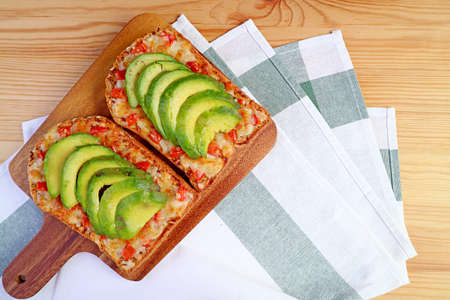 Top view of homemade grilled cheese toast with tomato and sliced avocado on wooden breadboard