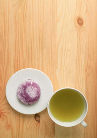Top View of Japanese Purple Sweet Potato Daifuku or Red Bean Paste Filling Rice Cake with Green Tea on Wooden Table
