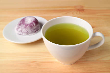 Closeup a Cup of Japanese Green Tea with Blurry Purple Sweet Potato Daifuku or Red Bean Paste Filling Rice Cake in Backdrop