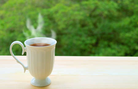 Cup of Hot Tea with Rising Steam with Blurry Green Foliage in the Backdrop