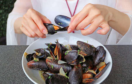 Woman Having her Steamed Mussels in White Wine by Using an Empty Mussel Shell to Grab Another Mussel's Meat Out Imagens