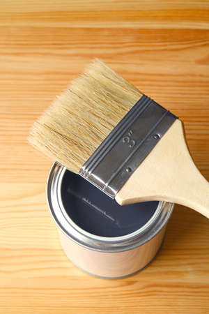 Paint brush on opened paint can isolated on wood plank