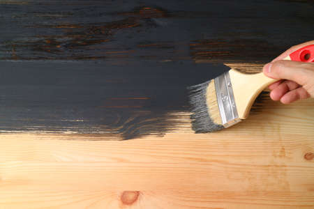 Man's hand painting surface of natural wood plank into black color