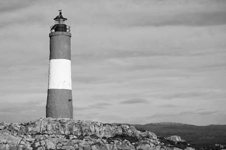 lighthouse on a rocky islands against cloudy sky in monochrome