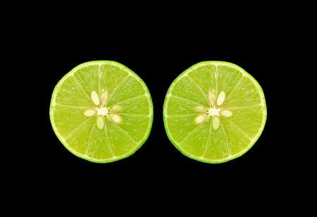 Pair of cross section fresh limes isolated s on black background