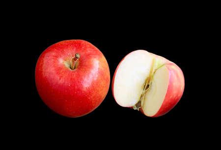 Fresh ripe red apple whole fruits with a half cut on black background