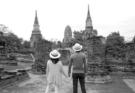Monochrome image of young couple visiting the amazing temple ruins in the Ayutthaya historical park, central region of Thailand