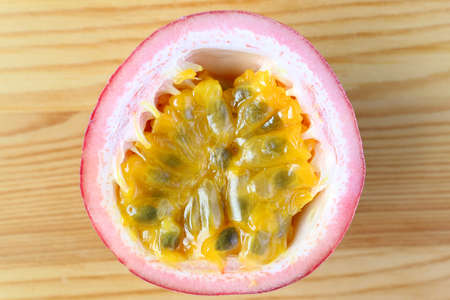 Top View of Half Cut Fresh Ripe Passion Fruit Isolated on Wooden Backdrop