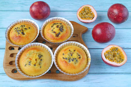 Fresh Baked Homemade Passion Fruit Muffins in Molds on Breadboard with Fresh Fruits Scattered on Pale Blue Table Imagens
