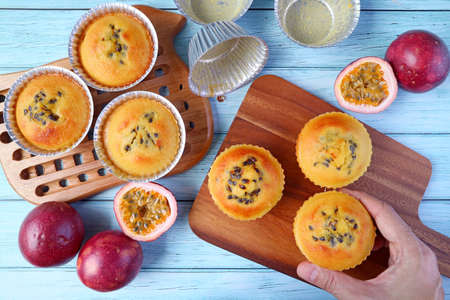 Hand Placing Fresh Baked Homemade Passion Fruit Muffins on Breadboard after Taking from the Molds Imagens
