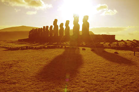 Sunrise over the silhouette of Moai statues at Ahu Tongariki celemonial platform on Easter Island, Chile, South America in golden color