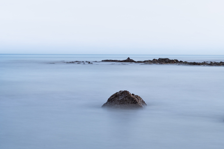 Blue sea long exposure with rocks in frame