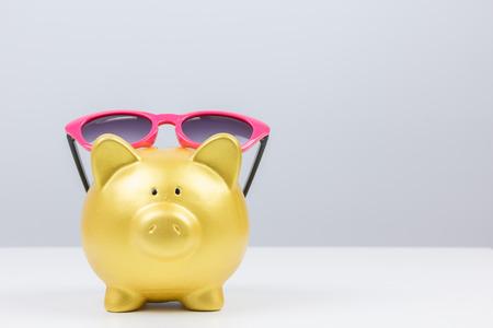 concept : saving for travel gold piggy bank wear sunglasses