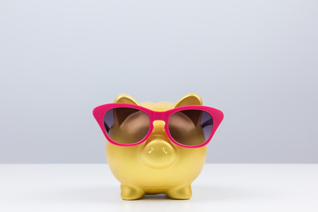 holiday budget: concept : saving for travel gold piggy bank wear sunglasses